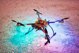 Unmanned quadrocopter landed on snow in winter evening poster