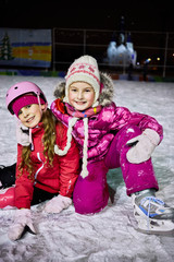 Two little girls sit embracing on skating rink ice in evening