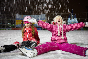 Two little girls sit on skating rink ice in evening