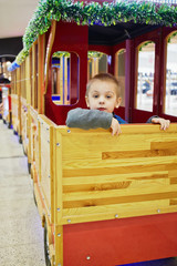 Little boy sits in wooden coach at children attraction
