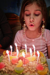 Little girl blows out candles on birthday cake