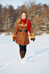smiling woman dressed in sheepskin fur coat walk