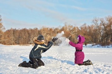 Two children play with snow on bright winter day