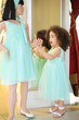 Pretty little girl in dress puts flower in hand of mannequin