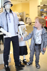 Pretty little boy holds hand of mannequin