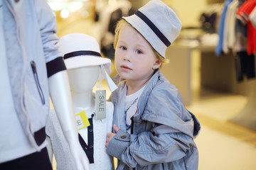 Cute little boy poses near two mannequins