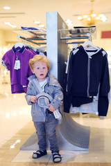 Surprised little boy stands near clothes hangers