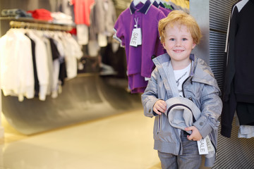 Smiling little boy stands near clothes hangers