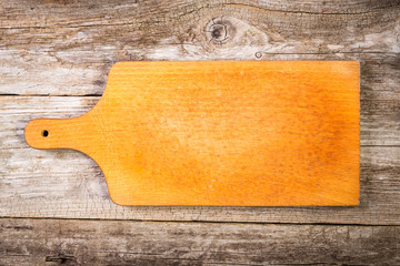 Empty vintage cutting board on food background.