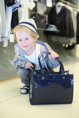 Little boy with bag sits near clothes hangers
