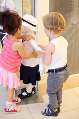 Little boy and girl repair hand to mannequin in store