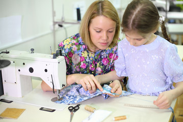 tailor sits at table with sewing machine and teaches girl