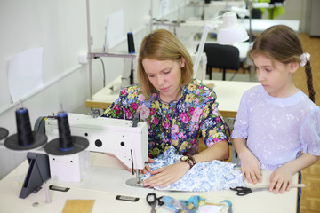 Female tailor sews at sewing machine and student girl looks
