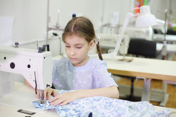 Student girl sews at white sewing machine in classroom