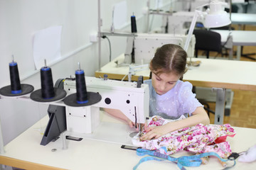 Student girl sews small dress at white sewing machine