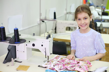 Smiling girl stands near table with sewing machine in classroom