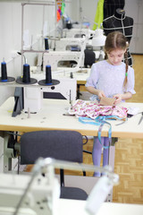 Girl stands near table with sewing machine and holds cloth