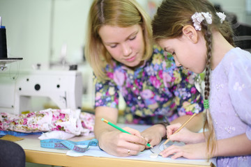 Female tailor teaches student girl use of templates