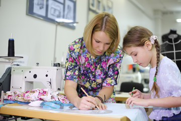 Female tailor shows student girl how use of templates
