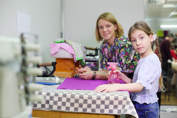 Female tailor and student girl prepare for irons new clothes