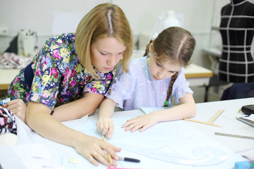 Female tailor teaches student girl how to draw patterns