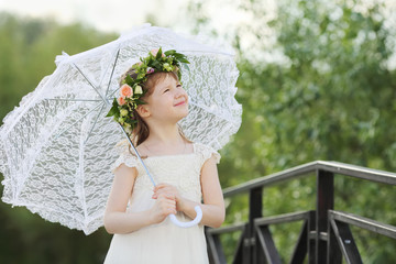 Little cute girl in white dress and wreath with umbrella