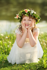 Little cute girl in white dress and wreath squats on grass