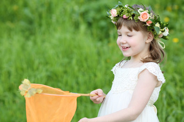 Little cute girl in white looks at butterfly sitting at net