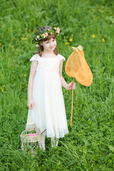 Little girl in white stands with butterfly net and coop