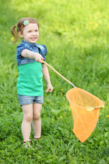 Little smiling girl holds orange butterfly net on meadow.