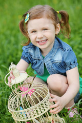 Little pretty girl holds coop with butterflies and smiles