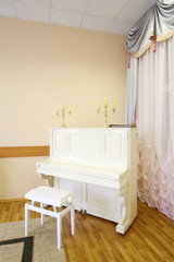 Beautiful white piano with yellow candles in light empty room.
