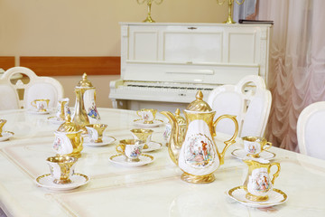 white piano with and table with set of porcelain dishes