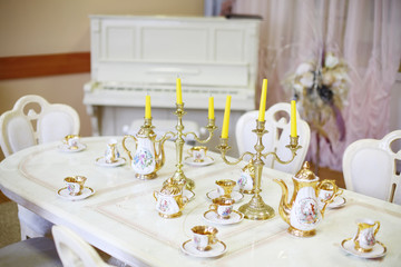 Table with set of porcelain dishes and candles