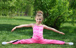 Little girl in pink performs exercise splitting legs apart