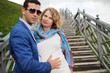 Pregnant woman in white stands on stairs and stylish man touches