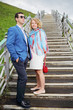Happy pregnant woman in white and stylish man stand on stairs