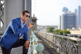 Handsome man in blue jacket and sunglasses with cigar stands