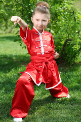 Little girl in red kimono for karate trains among greenery