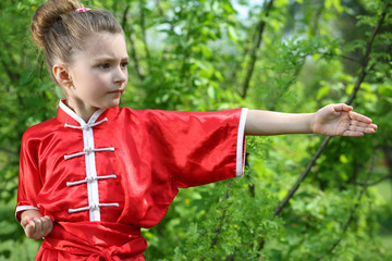 Little pretty girl in red kimono for karate performs exercises
