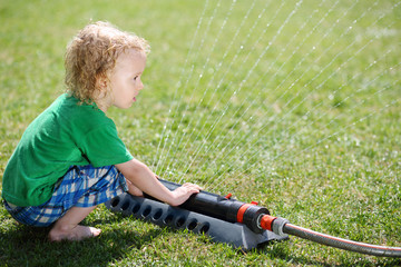 Little curly boy plays with sprinkler and looks at jets