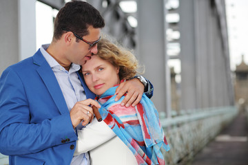 Stylish man with cigar embraces pregnant woman in white