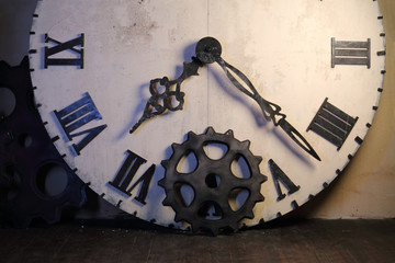 Half of big white clock with Roman dial and gearwheel in room