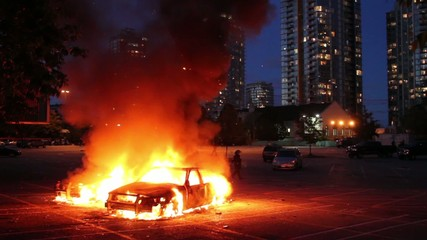 Two cars burn in parking lot with highrise at dusk