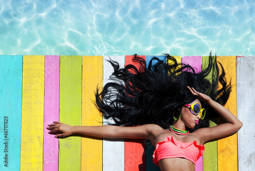 woman wearing sunglasses on a wooden pier background