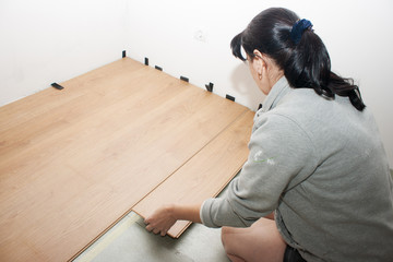 young woman puts laminate flooring