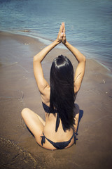 Woman is meditating in the lotus position on the beach