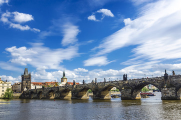 Charles bridge in Prague against a blue sky with clouds