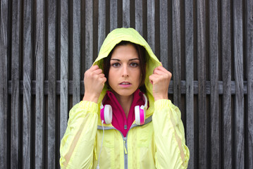 Serious female athlete wearing sport raincoat with hood