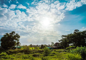 shining sun with lens flare. Blue sky with clouds in rural life